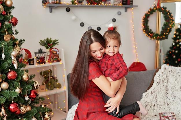 Famille près de sapin de noël. heureuse mère de famille et bébé près de sapin de noël en vacances. joyeux noël et bonnes fêtes! famille aimante avec des cadeaux dans la chambre.