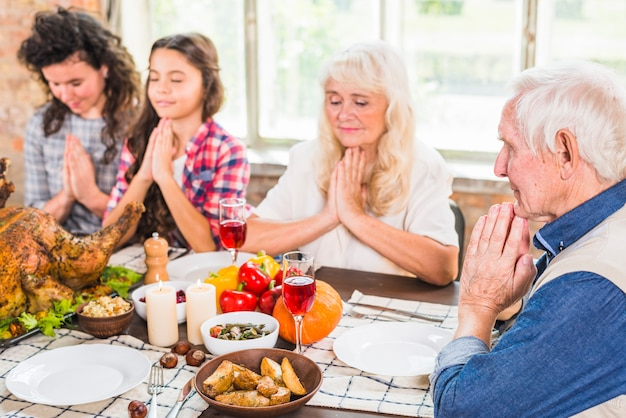 Famille priant avant de manger