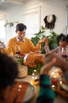 Famille priant ensemble avant le dîner de thanksgiving