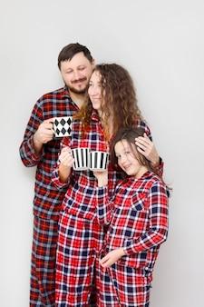 Famille en pyjama sur fond blanc. papa, maman et petite fille avec des tasses de thé.