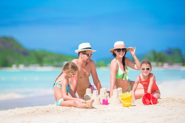 Famille de quatre faisant château de sable à la plage blanche tropicale