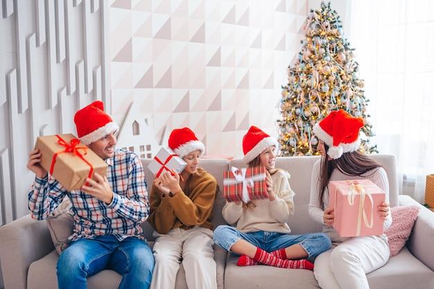 Famille de quatre personnes avec des cadeaux à noël à la maison