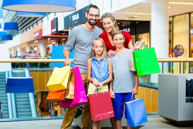 Famille de quatre personnes dans un centre commercial avec des sacs