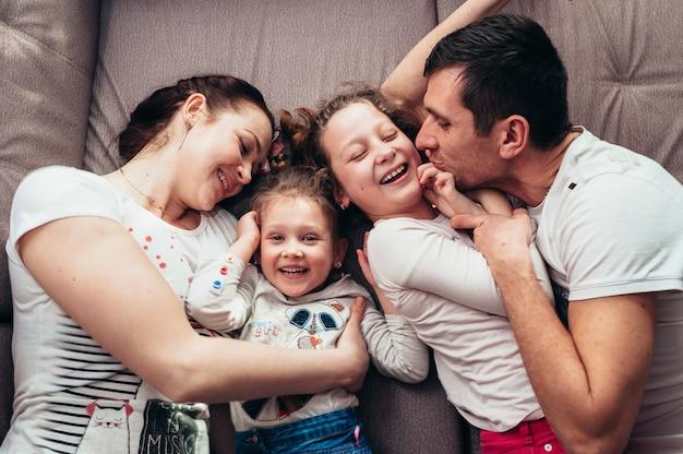 Une famille de quatre personnes avec des enfants bouclés étreint et rit en position couchée sur un canapé gris