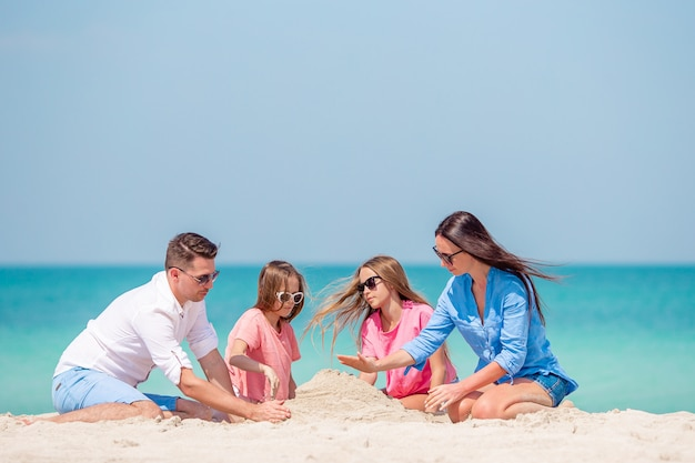 Famille de quatre personnes faisant un château de sable sur une plage tropicale blanche