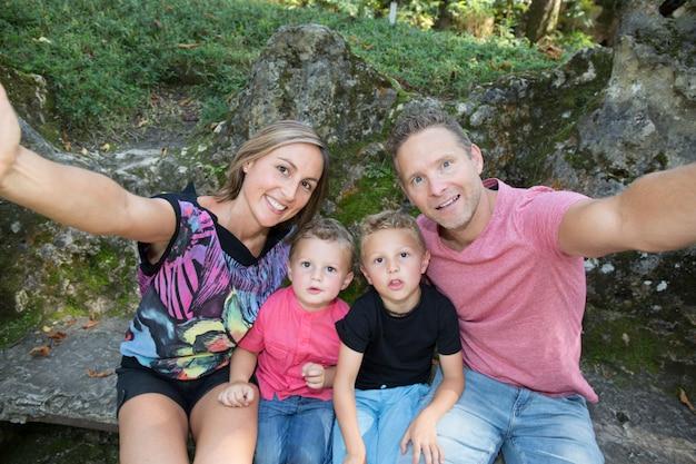 Une famille de quatre personnes fait un smartphone selfie en vacances au parc d'été