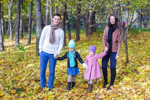 Famille de quatre personnes marchant dans un parc en automne par une chaude journée ensoleillée