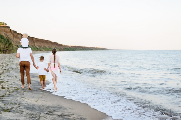 Famille de quatre personnes marchant le long du bord de mer. parents et deux fils. vue arrière