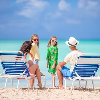 Famille de quatre personnes sur la plage en vacances dans les caraïbes.