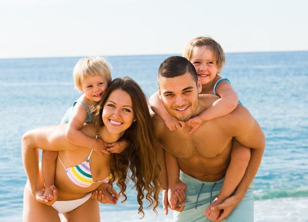 Famille de quatre personnes à la plage