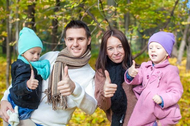 Famille de quatre personnes profitant des vacances d'automne et montrant un coup de pouce