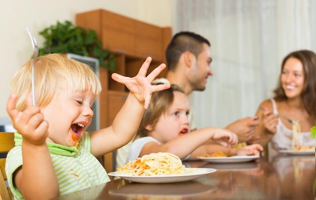 Famille de quatre personnes qui mangent des spaghettis