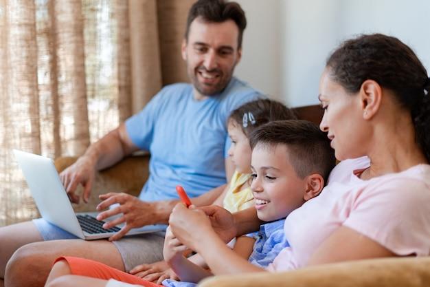 Une famille de quatre personnes s'amuse assis sur le canapé et utilise le wifi et la 5g en regardant des vidéos intéressantes, en jouant à des jeux et en regardant des dessins animés sur un ordinateur portable et un smartphone.