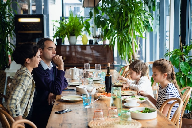 Une famille de quatre personnes en train de dîner dans un café
