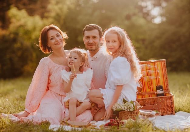 Famille de quatre personnes en train de pique-niquer dans le parc. heure d'été. espace de copie.