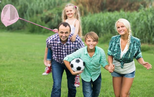 Famille de quatre reposant à la campagne