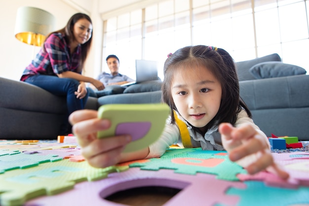 Famille de race mixte restant ensemble, père caucasien travaillant à la maison sur un canapé tandis que petite jolie fille mignonne jouant au jeu d'alphabet éducatif sur le sol et mère asiatique regardant avec amour. idée pour une famille chaleureuse