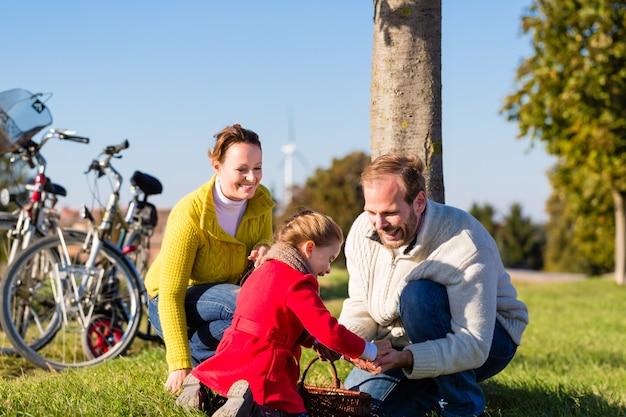 Famille ramassant des châtaignes lors d'un voyage à vélo