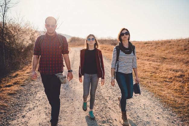 Famille en randonnée sur une route sale
