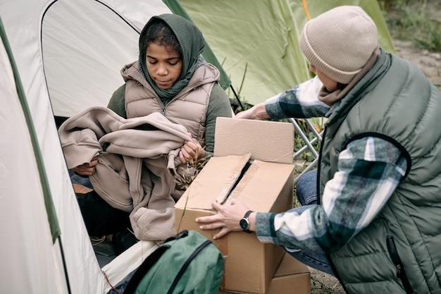 Famille de réfugiés s'installant dans la tente