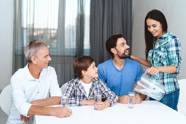 Famille regarde comme hôtesse de maison verse de l'eau douce.