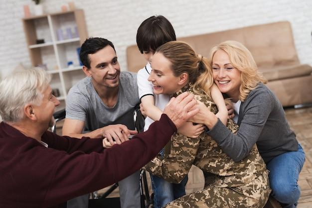 La famille rencontre une femme en tenue de camouflage à la maison.