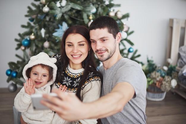 Famille réunie autour d'un sapin de noël faisant un selfie