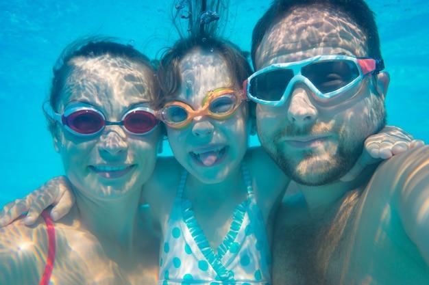 Famille s'amusant dans la piscine portrait drôle sous-marin vacances d'été