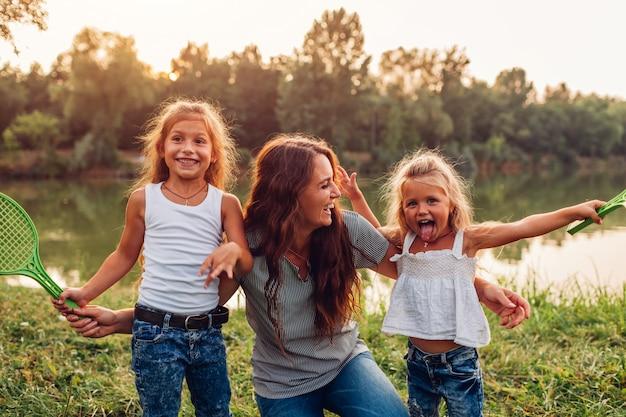 Famille s'amuser après avoir joué au badminton au bord de la rivière l'été au coucher du soleil. mère riant et grimaçant avec ses filles