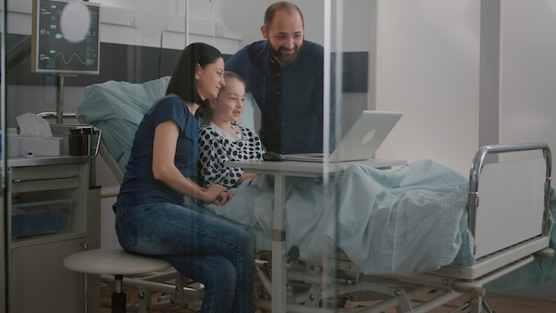 Famille saluant des amis distants lors d'une télécommunication par appel vidéo en ligne à l'aide d'un ordinateur portable à l'h...