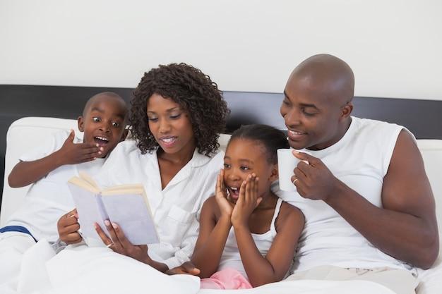 Famille se détendre ensemble dans le lit, livre de lecture