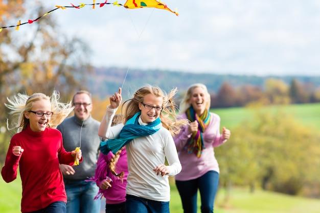 Famille se promener dans la forêt d'automne voler cerf-volant