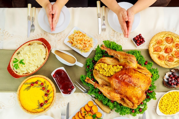 Famille se tenant la main au-dessus de la table et priant.