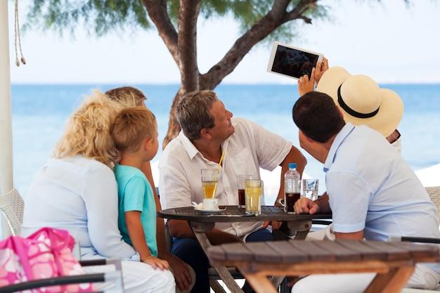 Famille selfie avec tablette dans un café en plein air