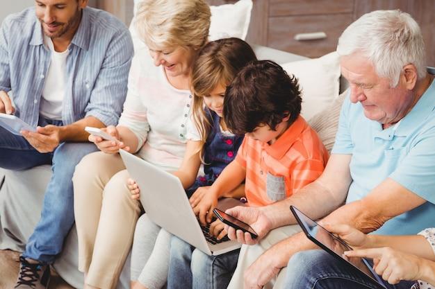 Famille avec ses grands-parents utilisant la technologie assis sur un canapé