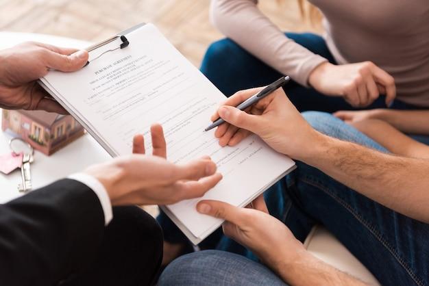 Famille signe un accord d'associé pour acheter une nouvelle maison.