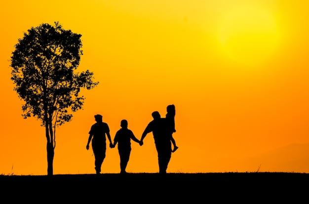Famille silhouette sur fond d'herbe au coucher du soleil