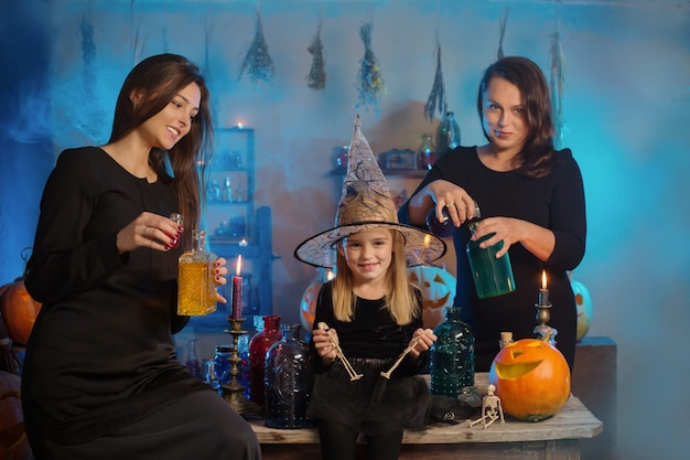 Famille de sorcières avec potions et citrouilles d'halloween à la maison