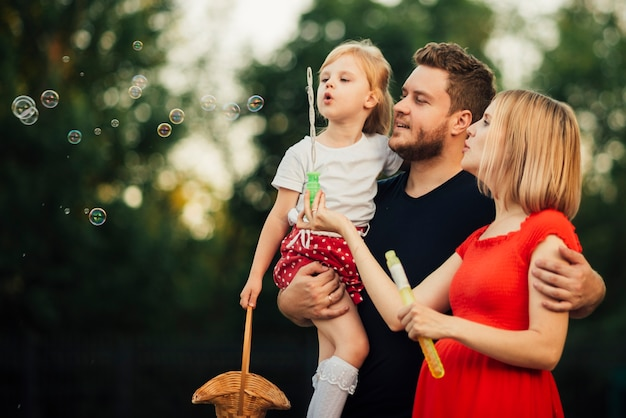 Famille soufflant des bulles de savon à l'extérieur
