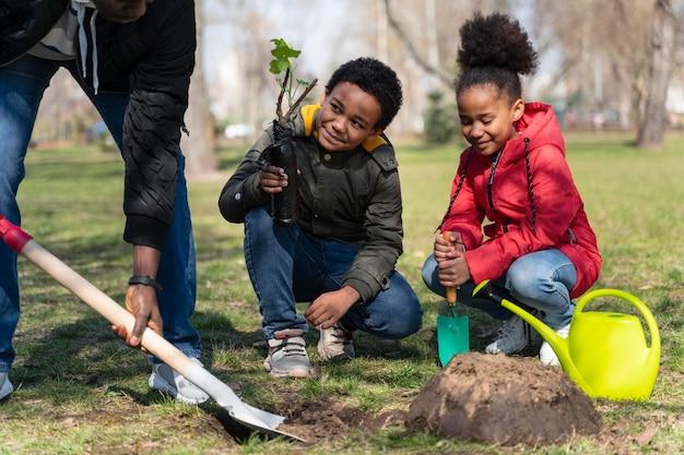 Famille souhaitant planter ensemble un arbre