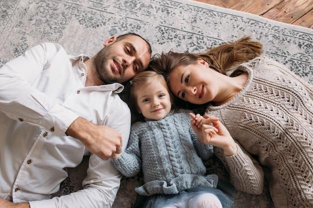 Famille souriant en position couchée sur le sol à la maison