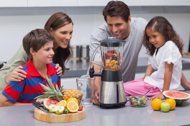 Famille souriante à l'aide d'un mélangeur