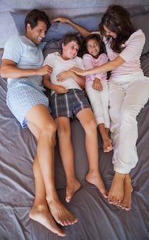 Famille souriante allongée sur le lit