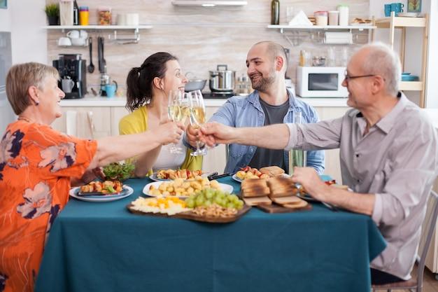 Famille souriante grillant avec des verres à vin pendant le déjeuner en famille dans la cuisine. pommes de terre assaisonnées savoureuses. heureux parents âgés.