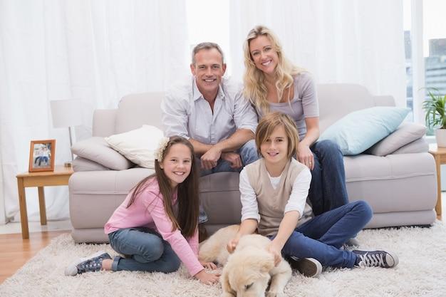 Famille souriante avec leur animal de compagnie jaune labrador sur le tapis