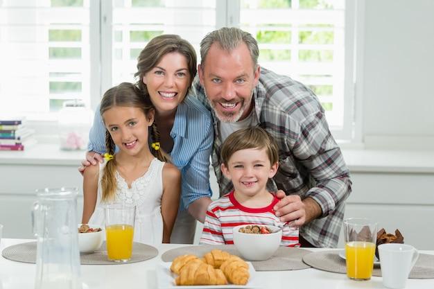 Famille souriante prenant son petit déjeuner dans la cuisine