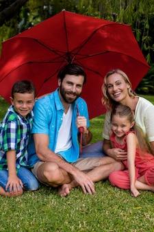 Famille souriante, séance, à, parapluie, dans, yard
