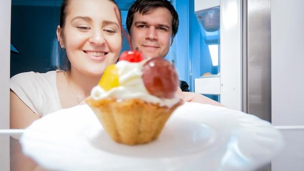 Famille souriante sortant un gâteau sucré du réfrigérateur dans la cuisine la nuit