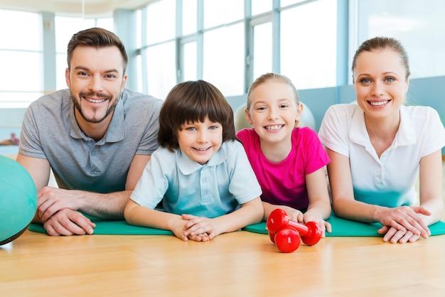 Famille sportive. bonne famille sportive se liant les uns aux autres en position allongée sur un tapis d'exercice ensemble