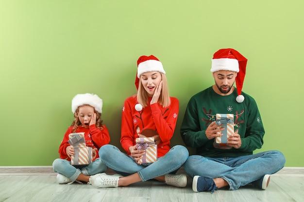 Famille surprise avec des cadeaux de noël assis sur le sol près du mur de couleur